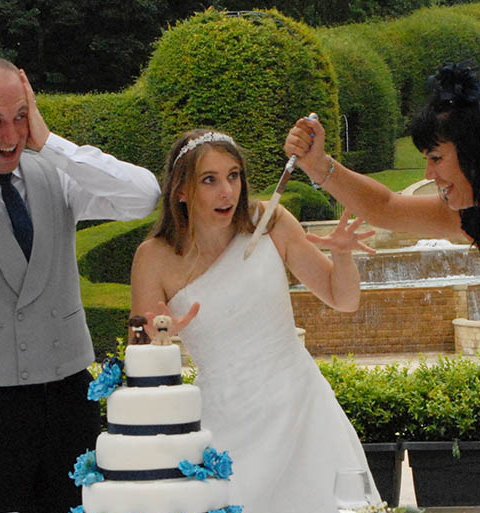 Guest at a wedding attacks cake with knife while bride and groom look shocked